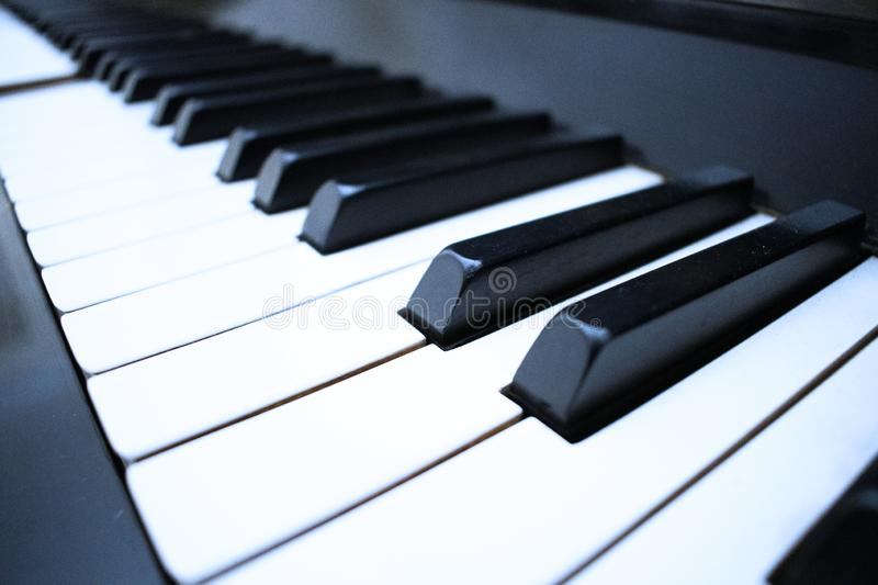 A hand playing with Piano keyboard background with selective focus. Cold color toned image stock photos