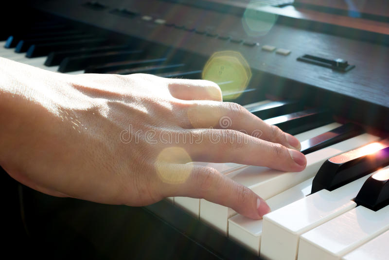 Hand playing piano. stock image