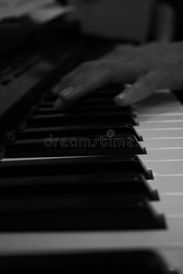 Hand playing piano perspective in black and white stock photo