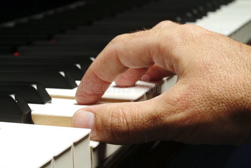 Hand plays piano stock photo