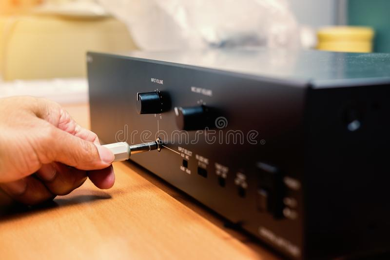 Hand plugs 3.5 mm audio stereo jack to amplifier. stock images
