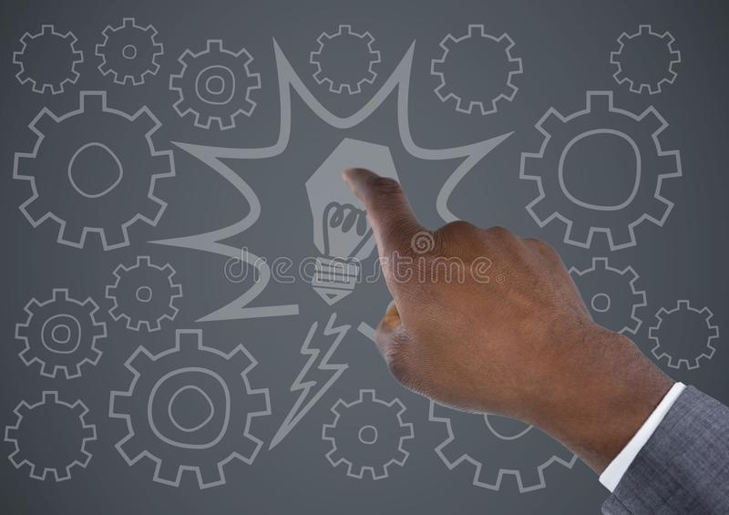 Hand pointing at lightbulb and cog doodles against grey background royalty free stock image