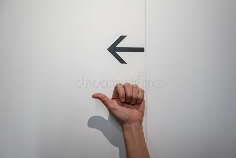 Hand pointing out for something with black arrow on whi. Te wall background stock image