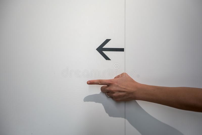 Hand pointing out for something with black arrow on whi. Te wall background stock photo