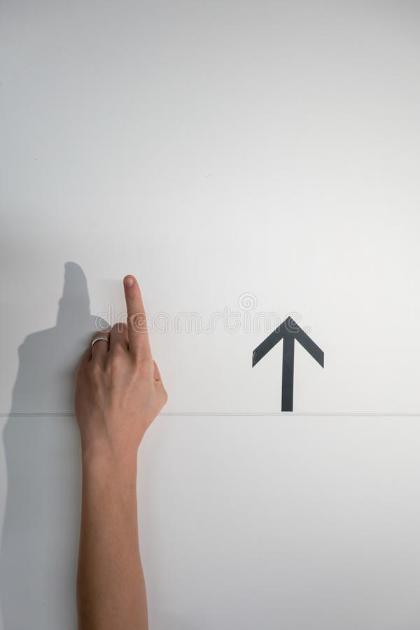Hand pointing out for something with black arrow on whi. Te wall background royalty free stock image
