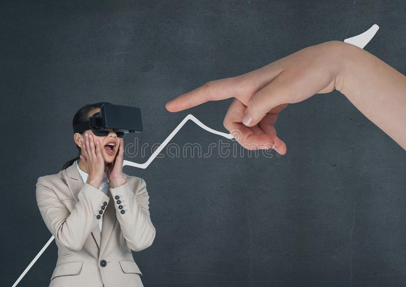 Hand pointing at surprised business woman in a VR headset against blue background with arrow. Digital composite of Hand pointing at surprised business woman in a stock images