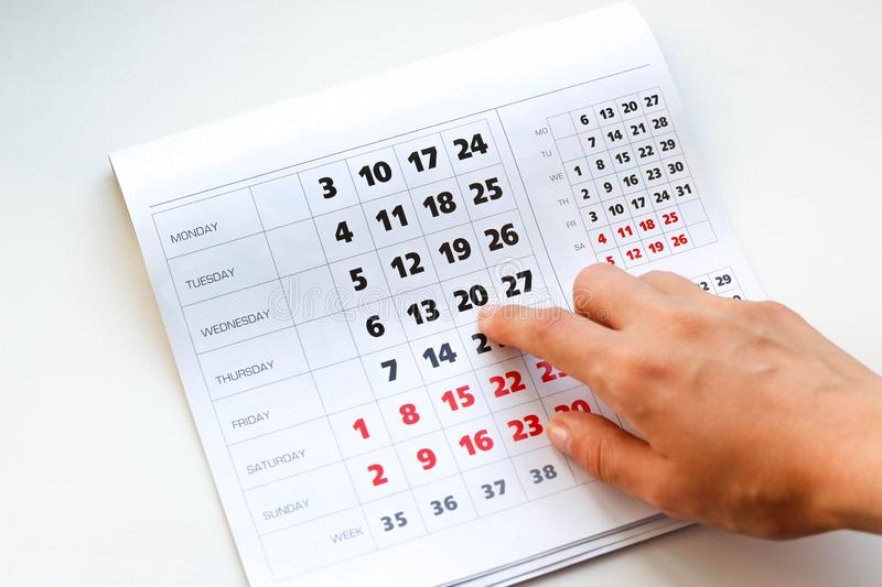 Hand pointing to the calendar. White calendar. Weekends are highlighted in red. Close up stock photos