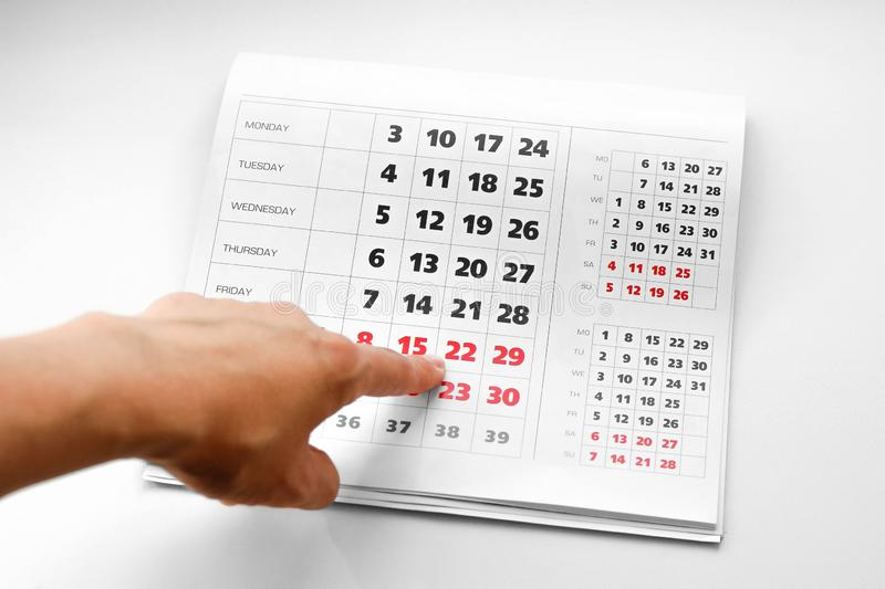 Hand pointing to the calendar. White calendar. Weekends are highlighted in red. Close up royalty free stock images