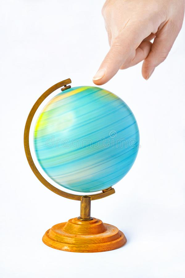 Hand pointing to a rotating globe. Female hand pointing to a rotating globe. The funny concept of choosing a place to relax or travel stock photography