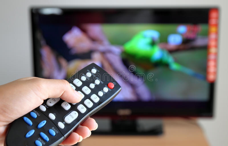 Hand pointing a tv remote control towards the tele stock image