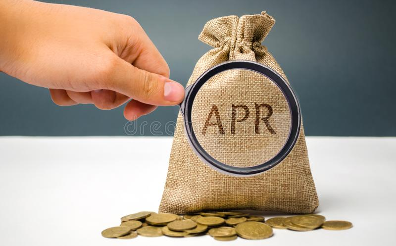 A hand points to a money bag with the word Apr. This is a financial fee, expressed as an annual rate. Applicable to loan, mortgage. Credit card. Commercial stock photos