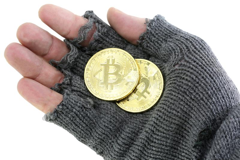 Hand of the poor with broken glove with two bitcoin coins. Bankrupt concept: hand of the poor with broken glove with two golden bitcoin coins stock photo