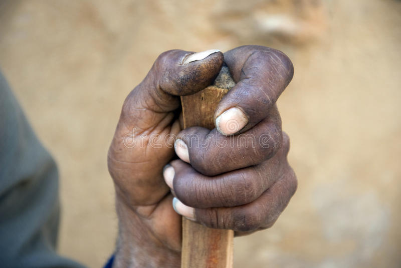 Hand of a poor, old man in Africa. Image of a dirty hand on a wooden walking stick of a poor, old man in Africa. It is a closeup image taken outside stock photos