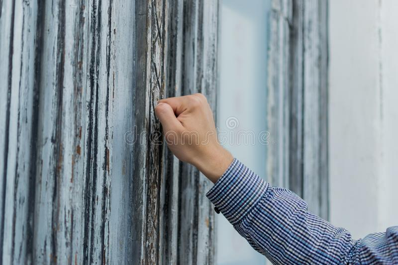 Hand postman in a plaid shirt knocking his fist at the old and shabby front door. Anybody home.  stock photography