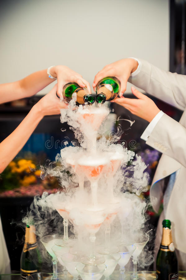 Hand poured champagne uphill from wine glasses and goes to the s stock images