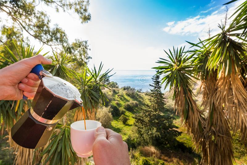 Hand Pouring Coffee In Cup against ocean, blue sky and exotic trees royalty free stock photo
