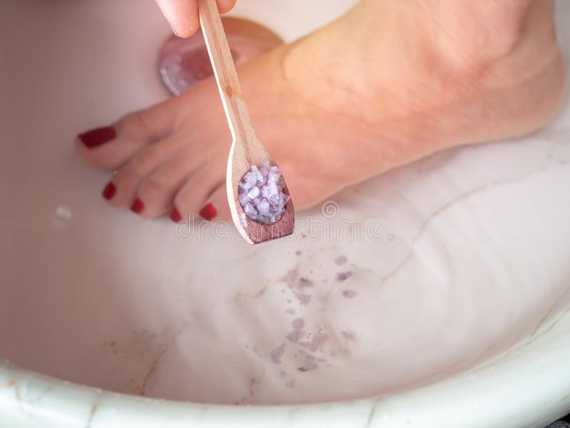 Hand pouring epsom salt from small wooden spoon and female feet in foot spa marble basin. Epsom salt foot soak concept royalty free stock image