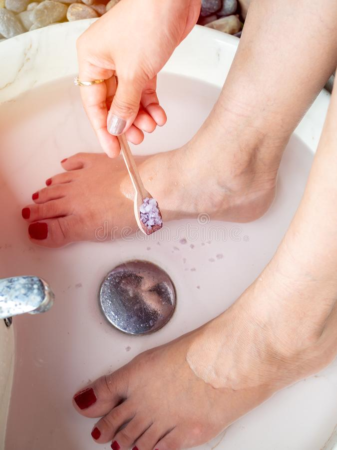Hand pouring epsom salt from small wooden spoon and female feet in foot spa marble basin. Vertical style. Epsom salt foot soak concept royalty free stock photo