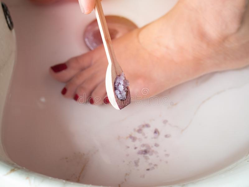 Hand pouring epsom salt from small wooden spoon and female feet in foot spa marble basin. Epsom salt foot soak concept stock photos
