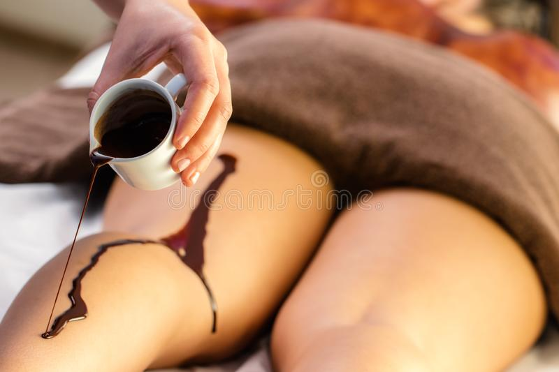 Hand pouring hot chocolate massage oil on female leg stock images