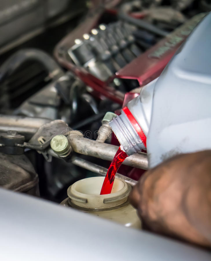 Hand pouring transmission fluid stock photos