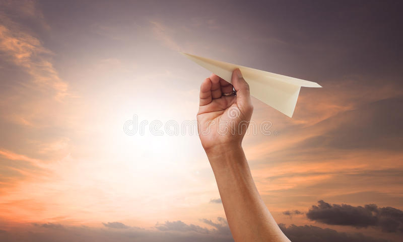 Hand preparing to throwing paper plane to mid air againt green g stock photography