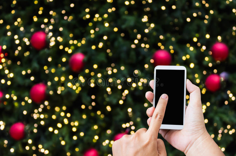 Hand press on big smartphone screen on Xmas New Year theme golden bokeh royalty free stock photos