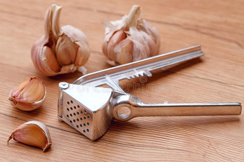 Hand press to crush the garlic. Metal hand press to crush garlic on the table stock photography