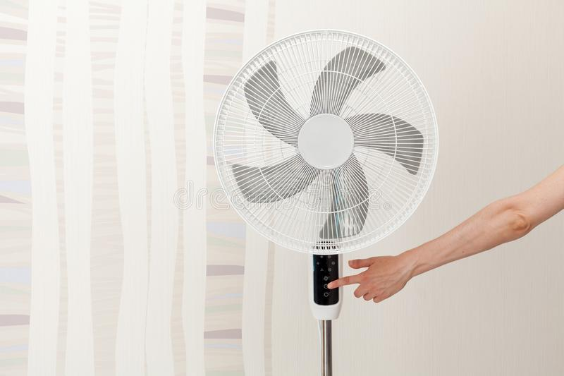 Hand presses the button on the control panel on the white electric fan. stock images
