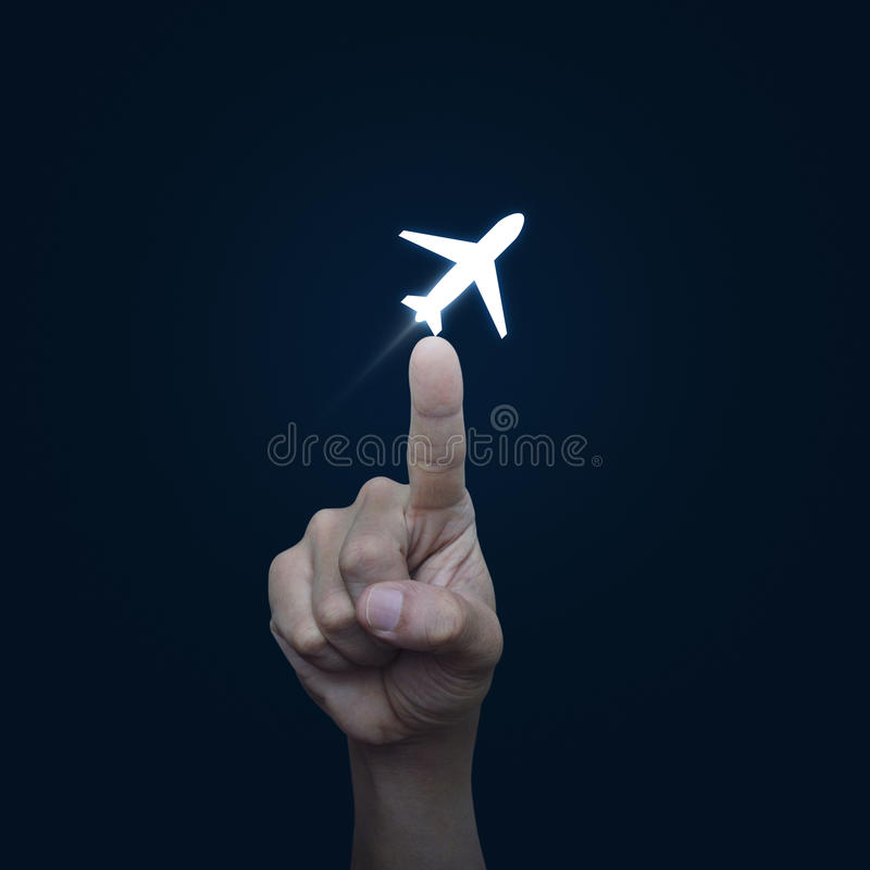Hand pressing airplane button on blue background, Select flight. Airplane concept royalty free stock images