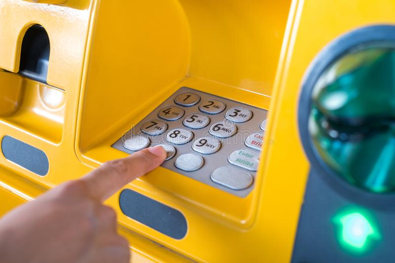 Hand pressing the code from the ATM focuses on the numbers and the finger area.  stock photos