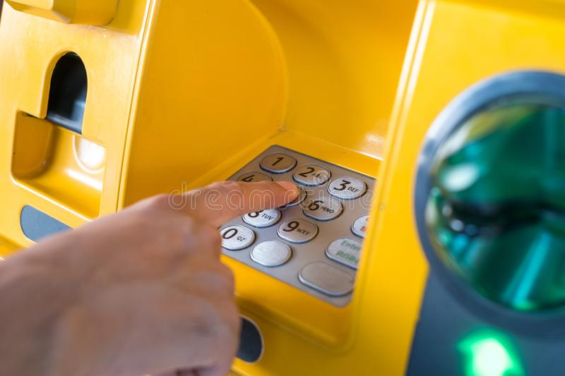 Hand pressing the code from the ATM focuses on the numbers and the finger area.  royalty free stock photography