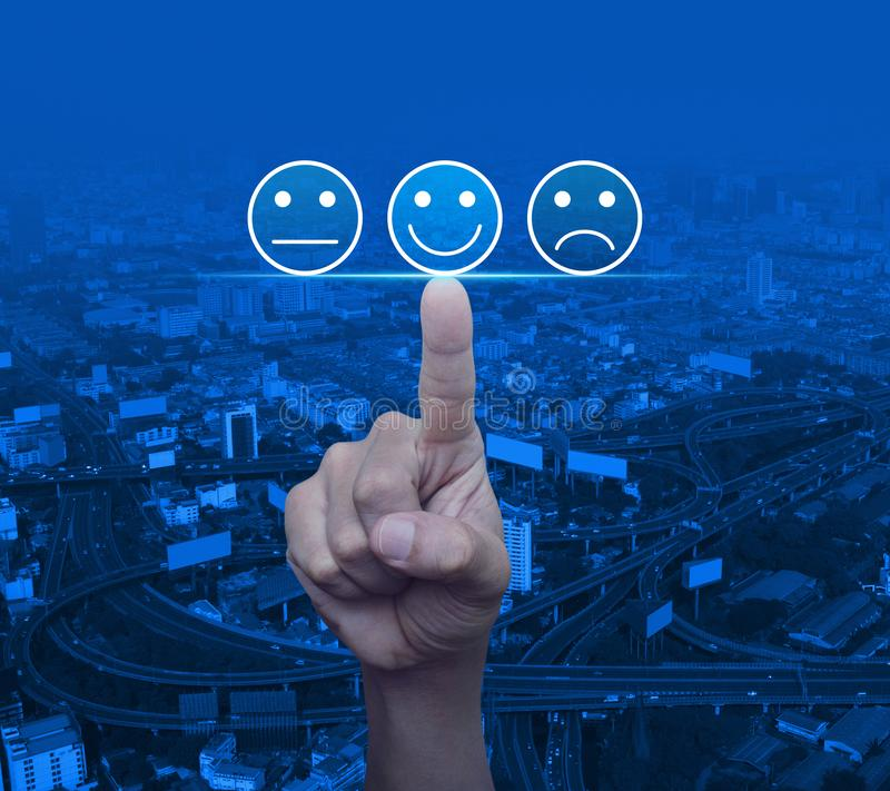 Business customer service evaluation and feedback rating concept. Hand pressing excellent smiley face rating icon over modern city tower, street, expressway and stock photo