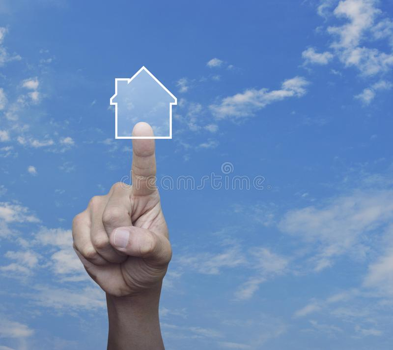 Real estate concept. Hand pressing house icon with copy space over blue sky with white clouds, Real estate concept royalty free stock photos