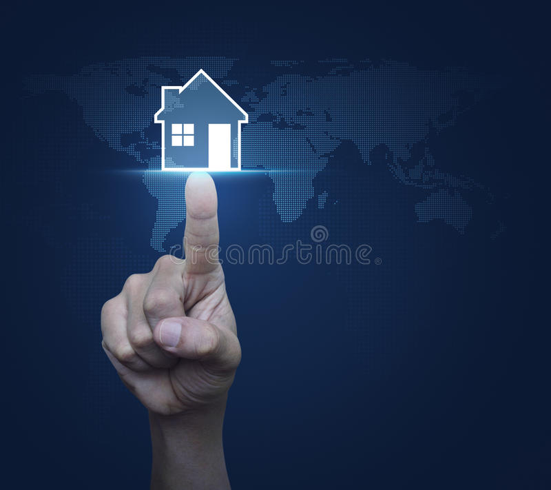 Hand pressing house icon with copy space over digital world map. Blue background, Real estate concept, Elements of this image furnished by NASA royalty free stock image