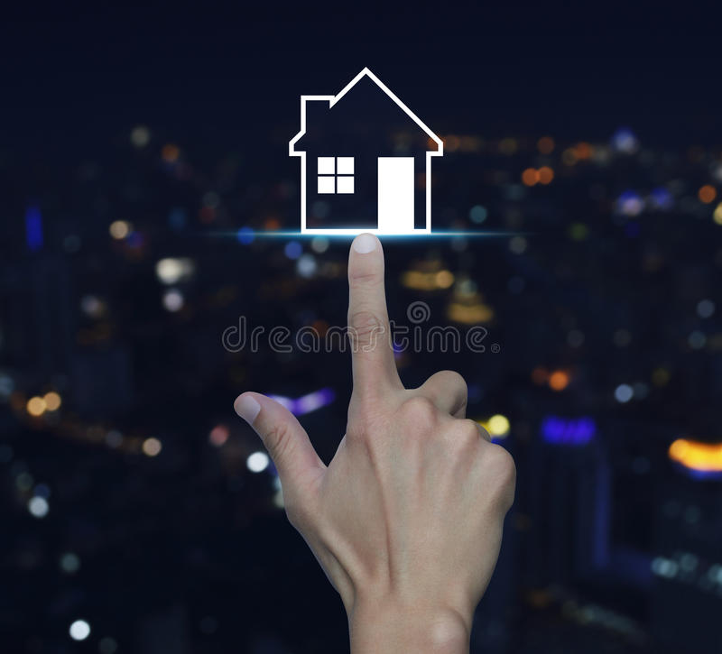 Hand pressing house icon over blur light city tower background,. Real estate concept royalty free stock image