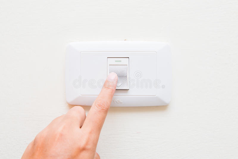 Hand pressing light power switch on wall stock photos