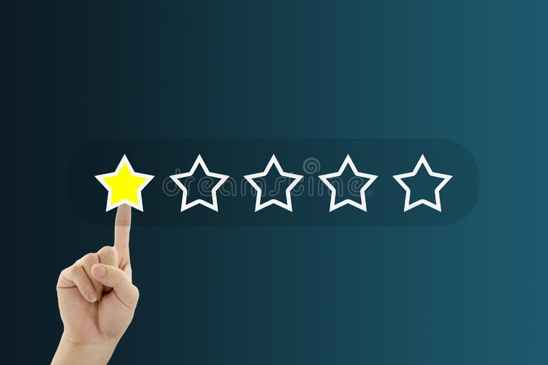 Hand pressing one yellow star for giving best service ranking. Customer Feedback Concept : Hand pressing one yellow star for giving best service ranking royalty free stock photography
