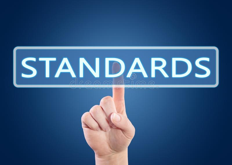 Standards text concept. Hand pressing Standards button on interface with blue background stock photos