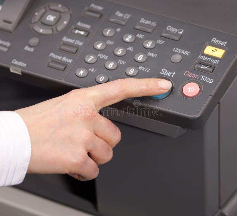 Hand pressing Start on copy machine. Hand pressing Start button on copy machine stock image