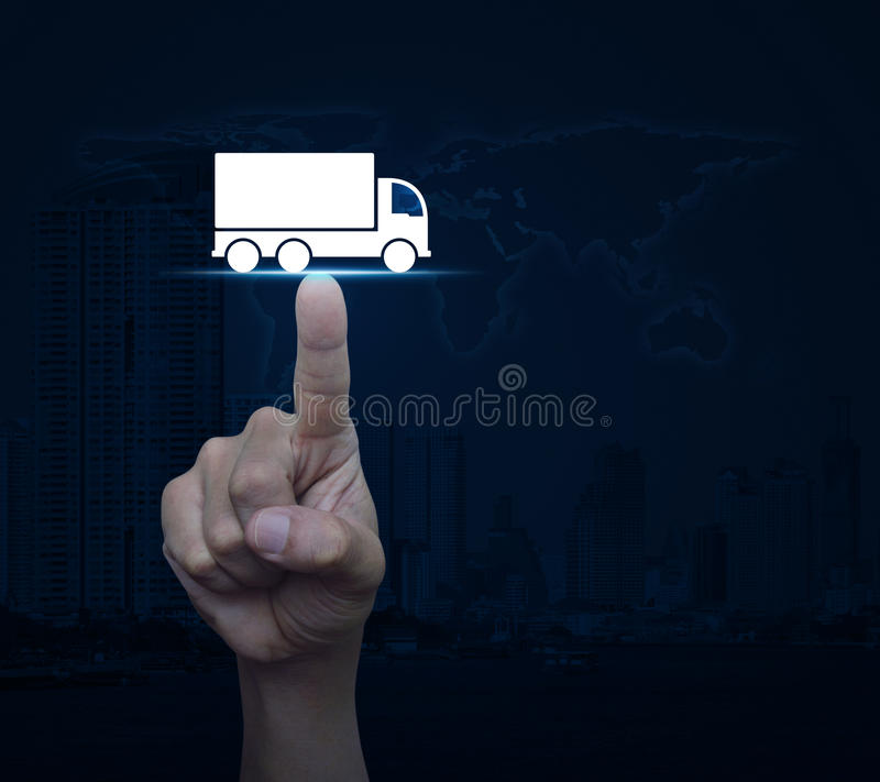 Truck transportation service concept, Elements of this image fur. Hand pressing truck flat icon over world map and modern city tower, Business transportation stock image