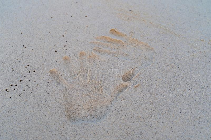 Hand print on the white sand royalty free stock photo