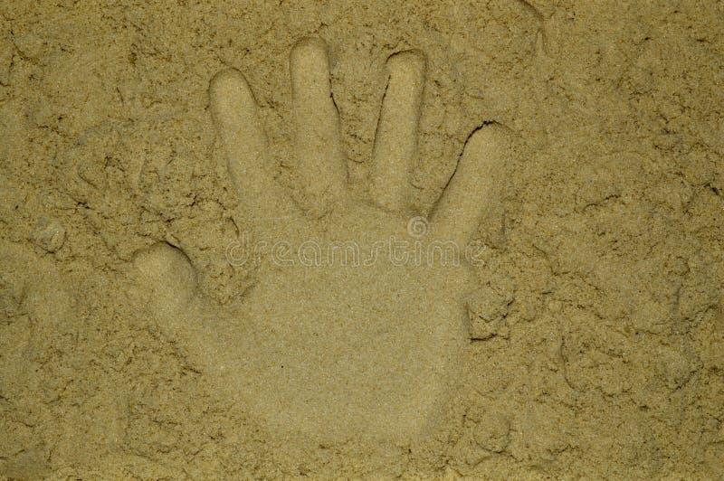 Hand print on yellow sand royalty free stock photos