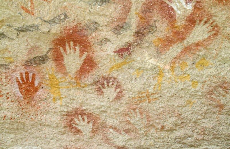 Hand prints on a cave wall cueva de las manos royalty free illustration