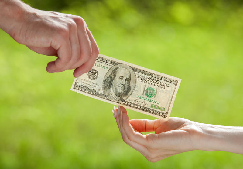 Hand proposing dollar banknote. To the other hand, light green background stock images