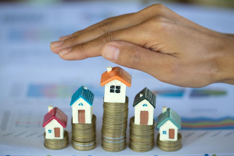 Hand protection, house model on top of stack of money as growth of mortgage credit, Concept of property management. Invesment and. Risk Management royalty free stock photos