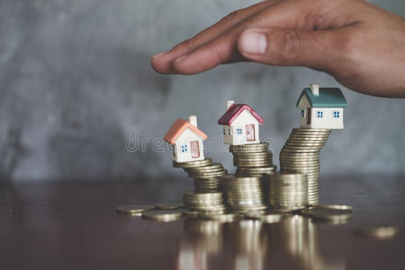 Hand protection, house model on top of stack of money as growth of mortgage credit, Concept of property management. Invesment and. Risk Management, Copy space royalty free stock image