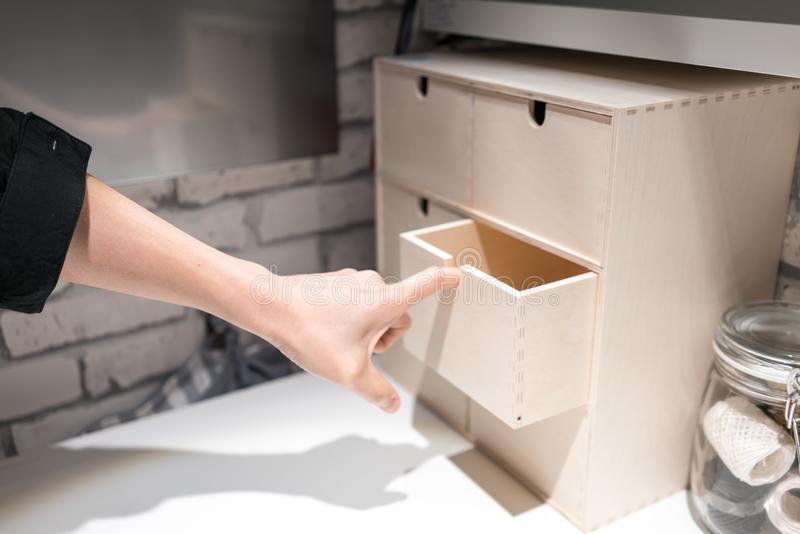 Hand pulling a drawer of mini wooden storage chest box on white royalty free stock photography