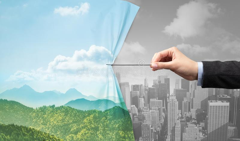 Hand pulling nature cityscape curtain to gray cityscape. Environmental protection concept royalty free stock photos