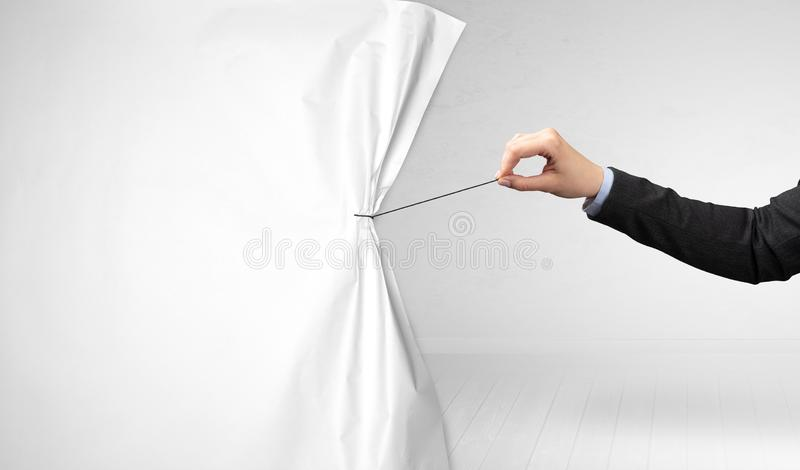 Hand pulling white paper curtain. Changing scene concept royalty free stock photo